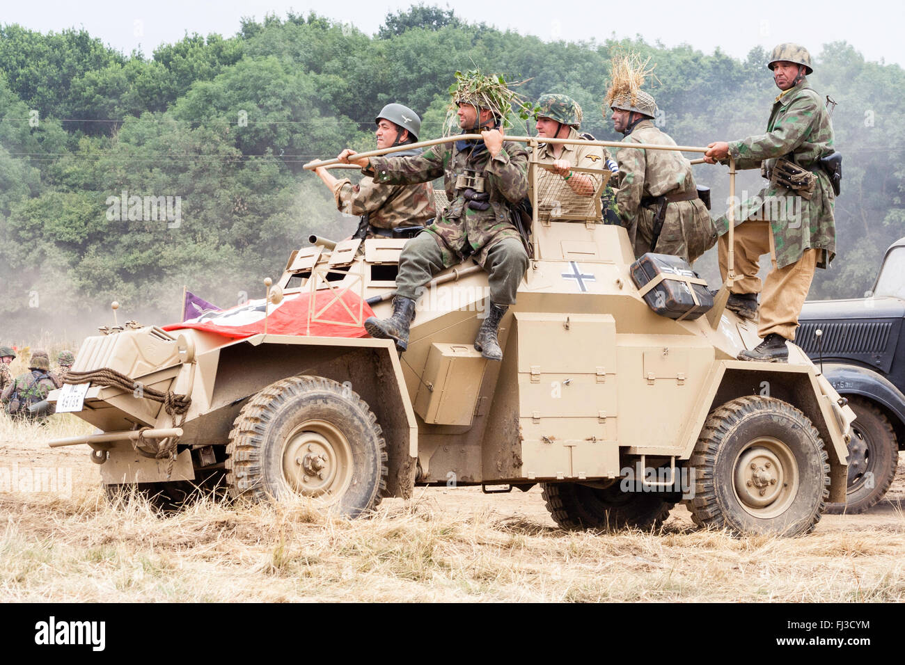Second world war re-enactment. German Africa Korps Sdkfz 222 armoured car, with Nazi flag draped on front and soldiers - Stock Image