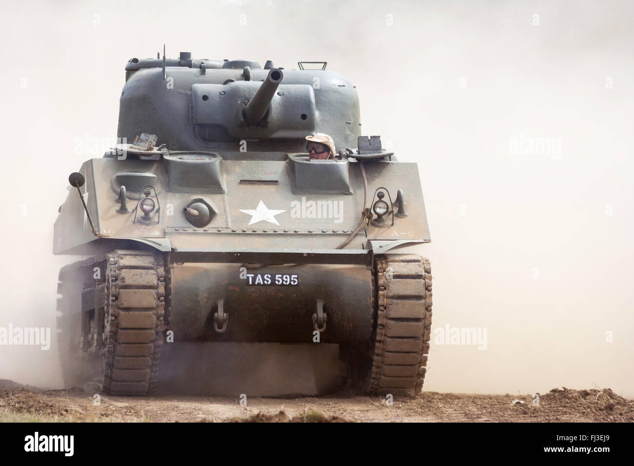 Second World War re-enactment. American M4 Sherman tank coming towards viewer at speed with lots of dust behind - Stock Image