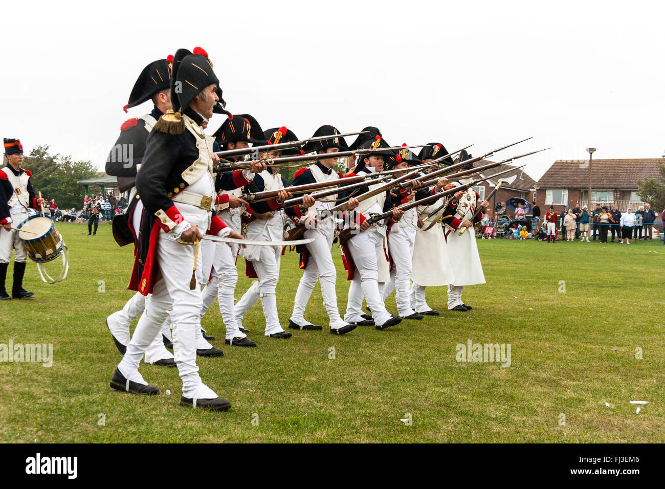 Napoleonic war re-enactment. French Imperial Guards with office in foreground, advancing in line, at the ready with - Stock Image