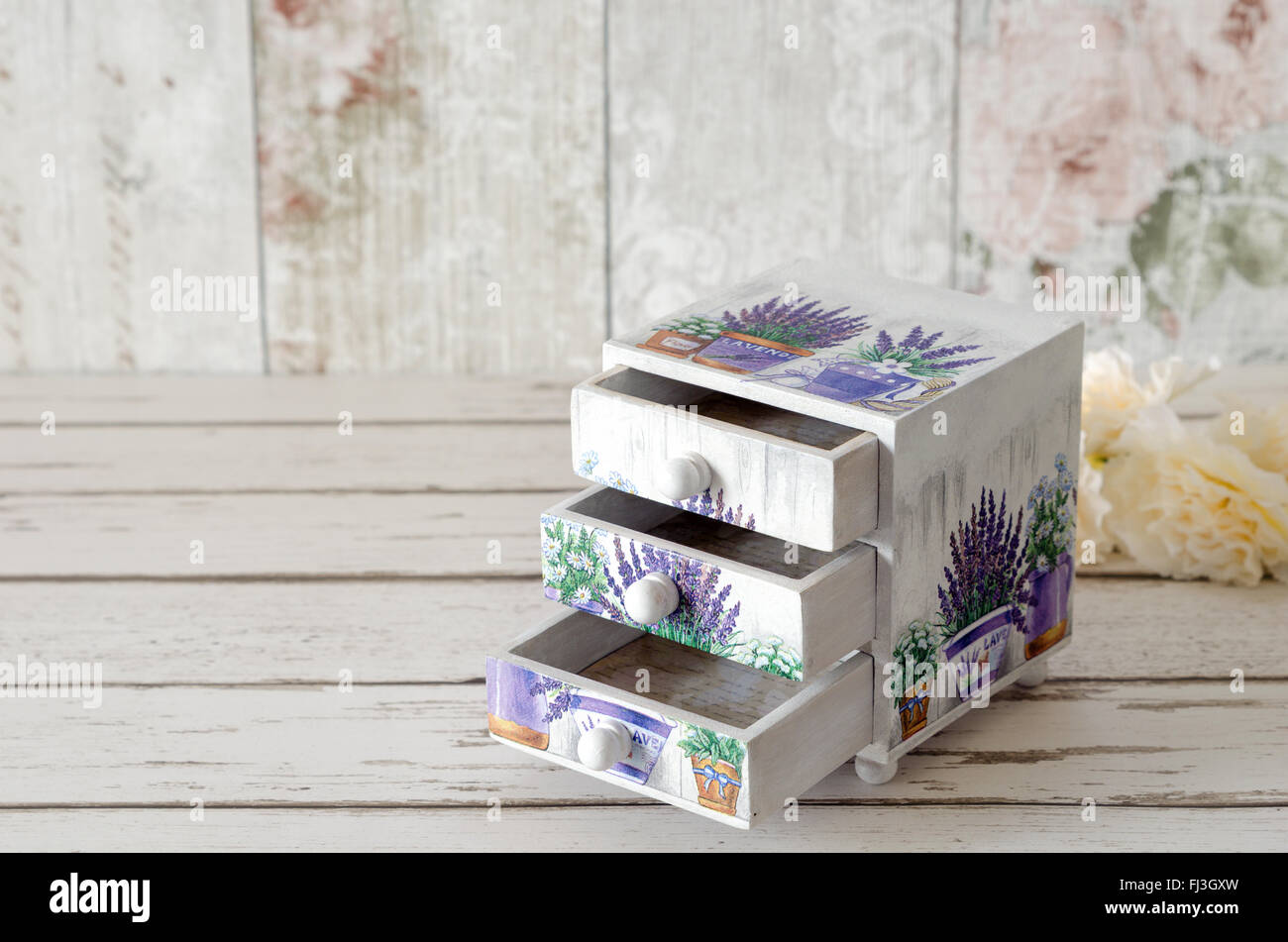 A handmade chest of trinket drawers decoupaged with vintage paperwith pots of Lavender on a rustic wooden background - Stock Image