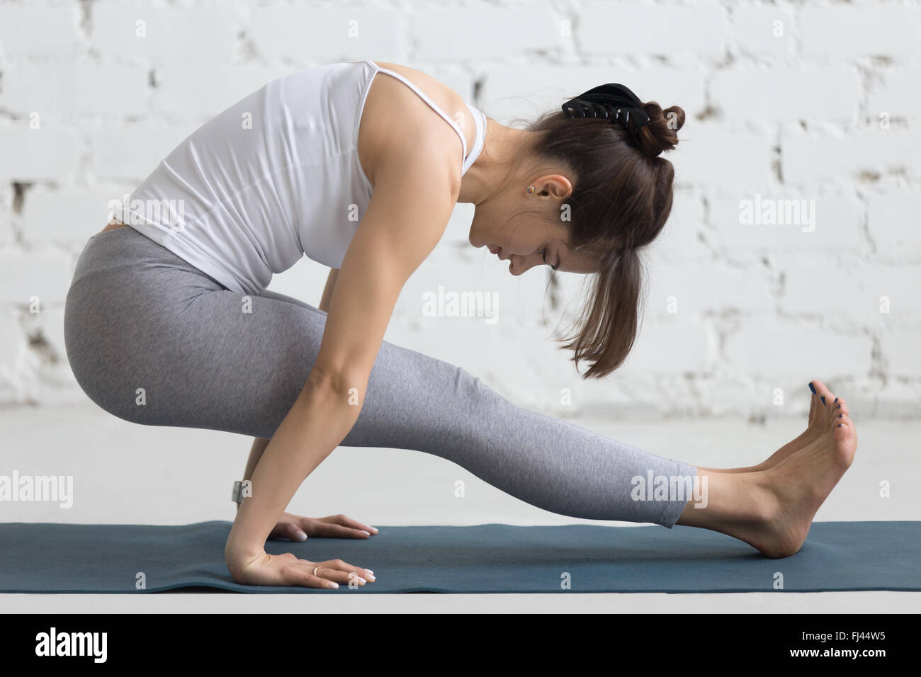 Beautiful young woman working out in loft interior on blue mat, doing yoga exercise for strong arms and abs, full - Stock Image