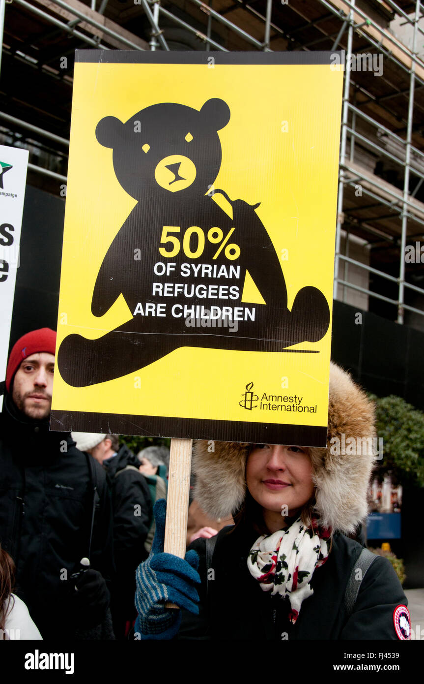 Stop Trident Demonstration  organised by CND.  A young woman holds a placard saying '50% of Syrian refugees - Stock Image