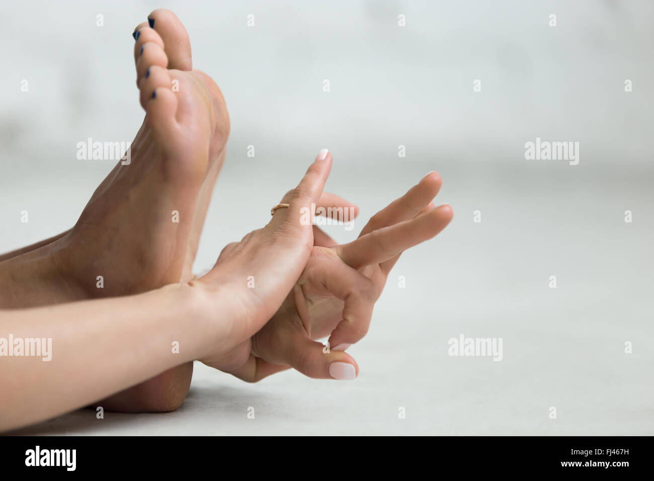Beautiful young woman working out indoors, doing yoga exercise, stretching, holding hands in Gyan Mudra - Mudra - Stock Image