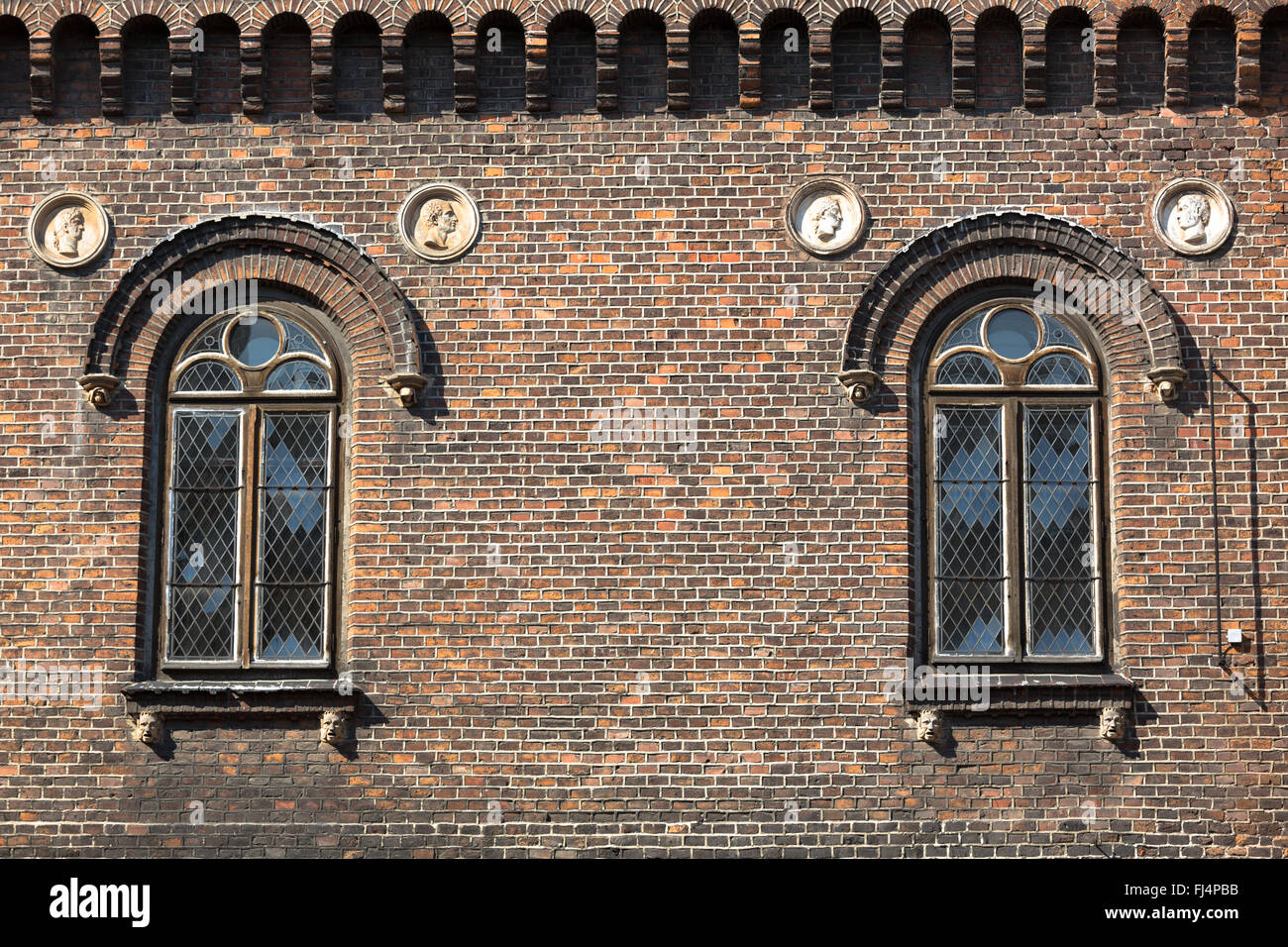 Cross hatch styled windows on a brick building - Krakow, Poland - Stock Image