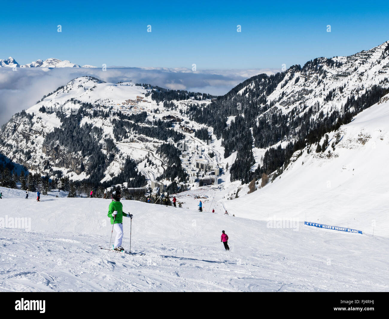 Skiers on snow slopes in Le Grand Massif ski area above Alpine skiing resort of Flaine, Haute Savoie, Rhone-Alpes, - Stock Image