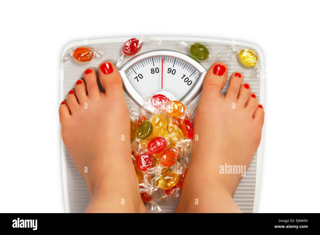 Photo of bathroom scale with candy - Stock Image