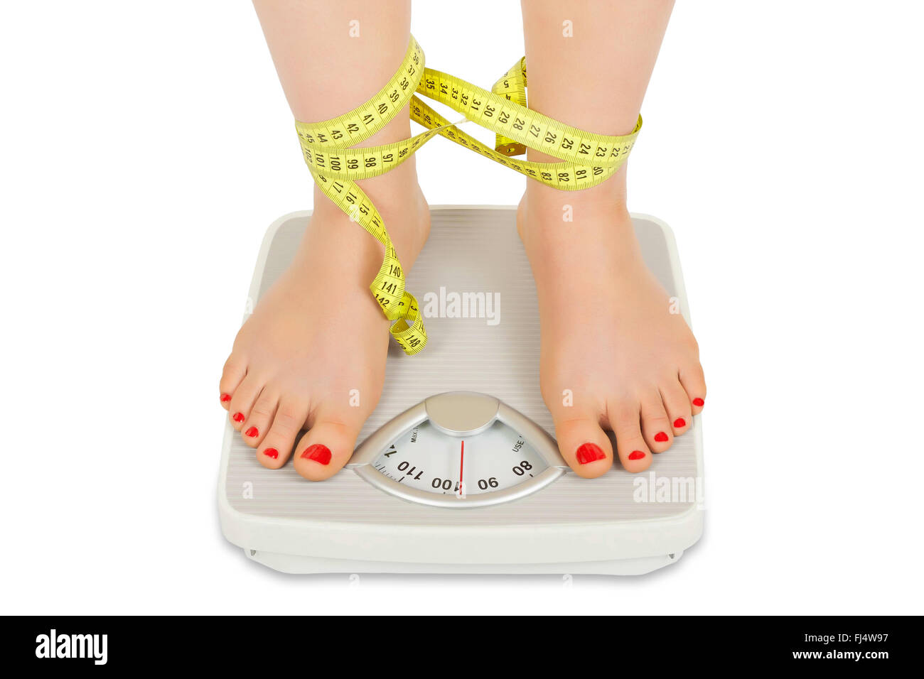 Photo of female foot on bathroom scale tied with tape meter isolated on white background - Stock Image