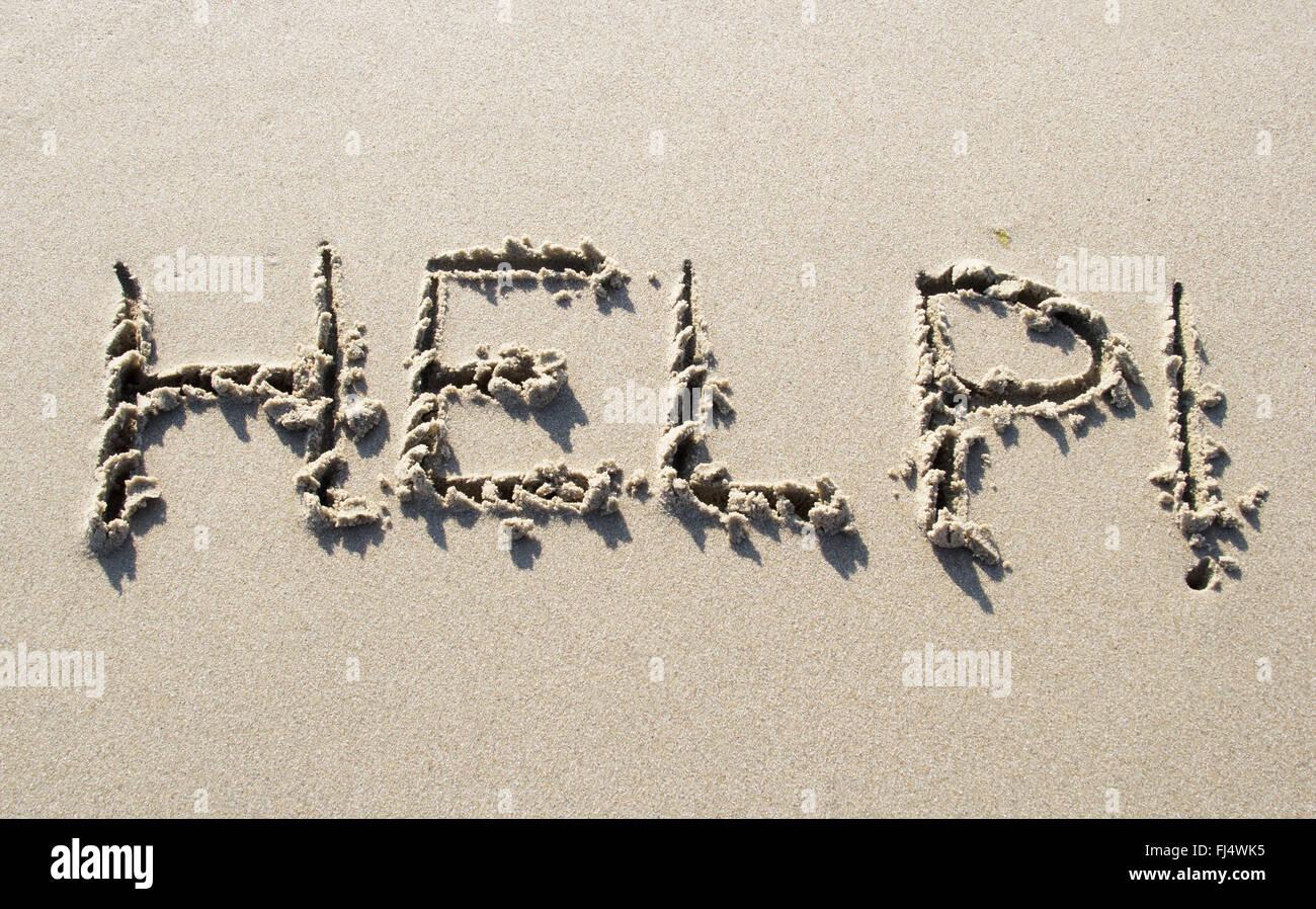 Help written on sand beach - Stock Image