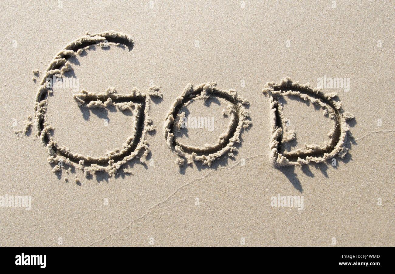 'God' written on sand beach - Stock Image
