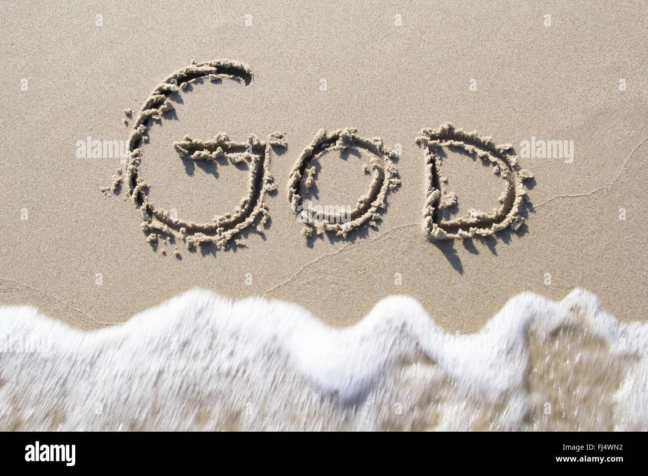 'God' written in sand - Stock Image