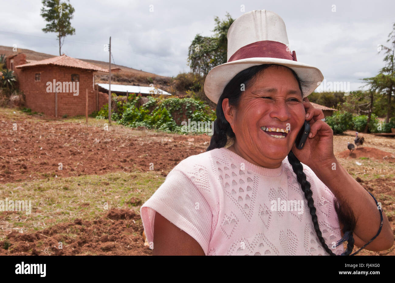 cheerful looking female Peruvian phoning in a field, portrait, Peru, Chinchero - Stock Image