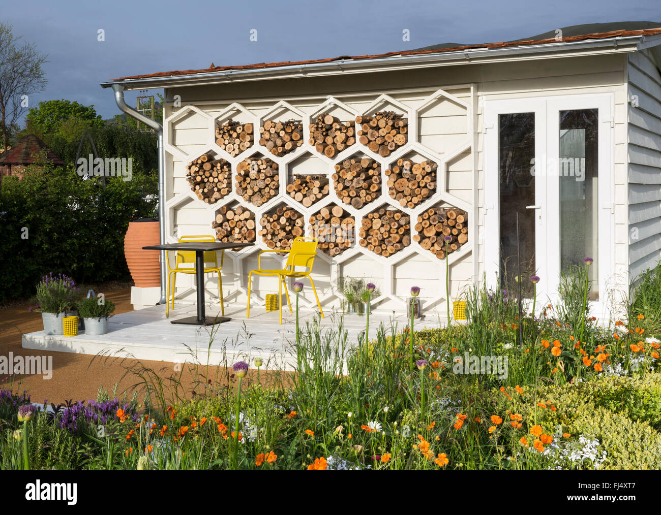Garden summerhouse with hexagonal structures insect hotels habitat, wooden deck with table and chairs, bee friendly - Stock Image