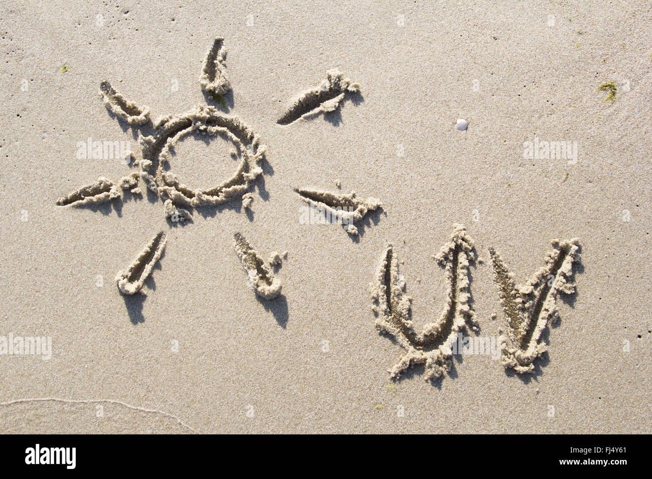 Symbol of sun drawn in sand - Stock Image