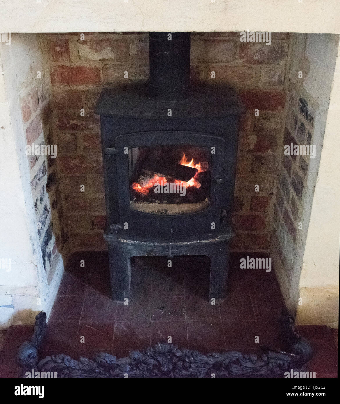 fireplace black brick old burnt smoke free heat close coal wood fire flame glow log light sparks energy old domestic - Stock Image