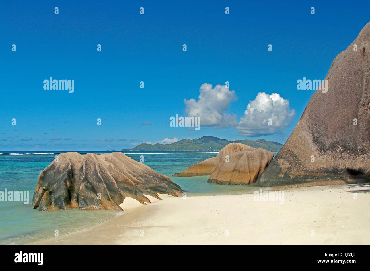 beach with granite rocks and view onto the island Praslin in the background, Seychelles, La Digue, Anse Source d - Stock Image