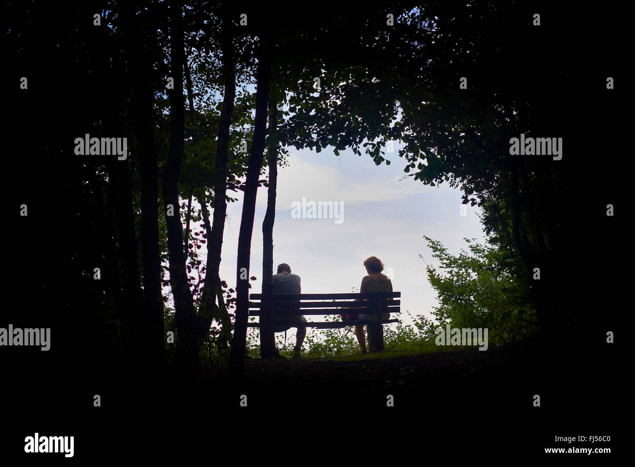 man and woman sitting on a bench at the end of a long and arduous journey, Volme Hoehenring, Germany, North Rhine - Stock Image