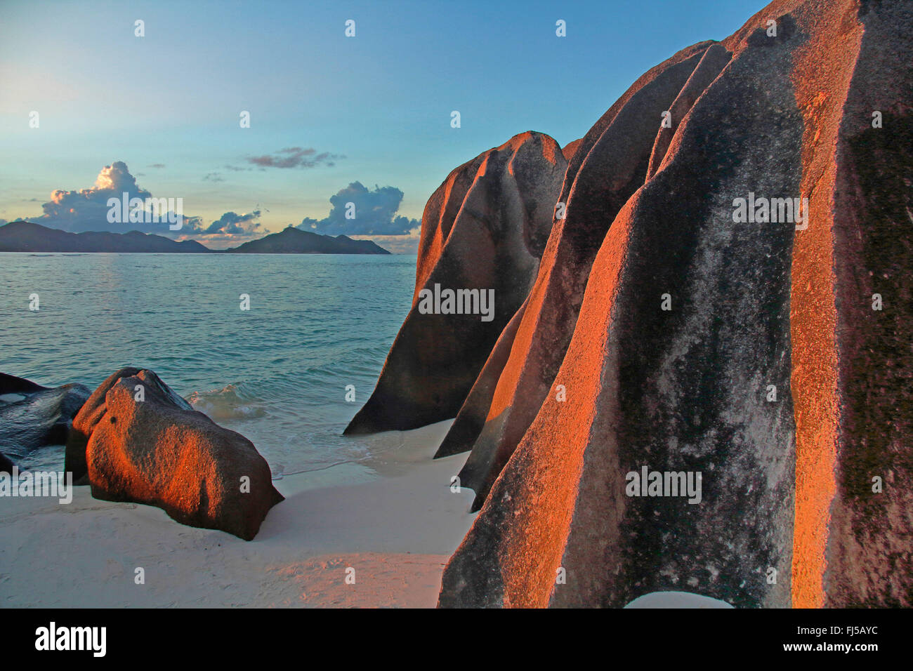 beach with rutted granite rocks and view onto the island Praslin in the background, Seychelles, La Digue, Anse Source - Stock Image