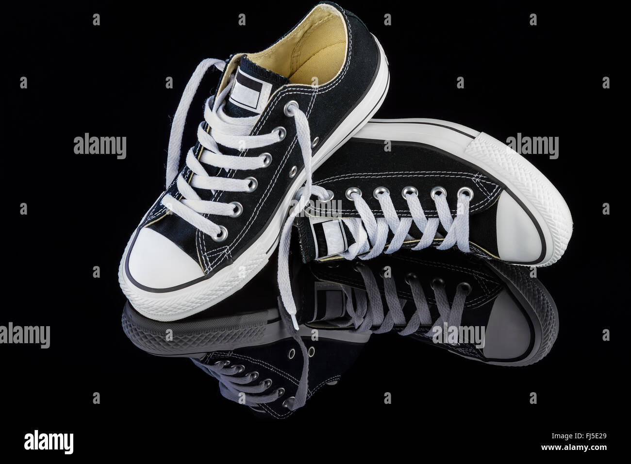 Black sneakers on black background - Stock Image