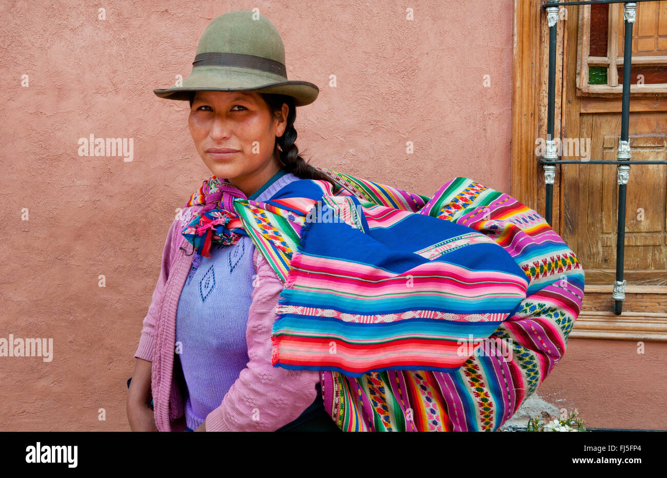 woman in traditional clothing carrying piggyback her baby in a sling, portrait, Peru, Pisaq - Stock Image