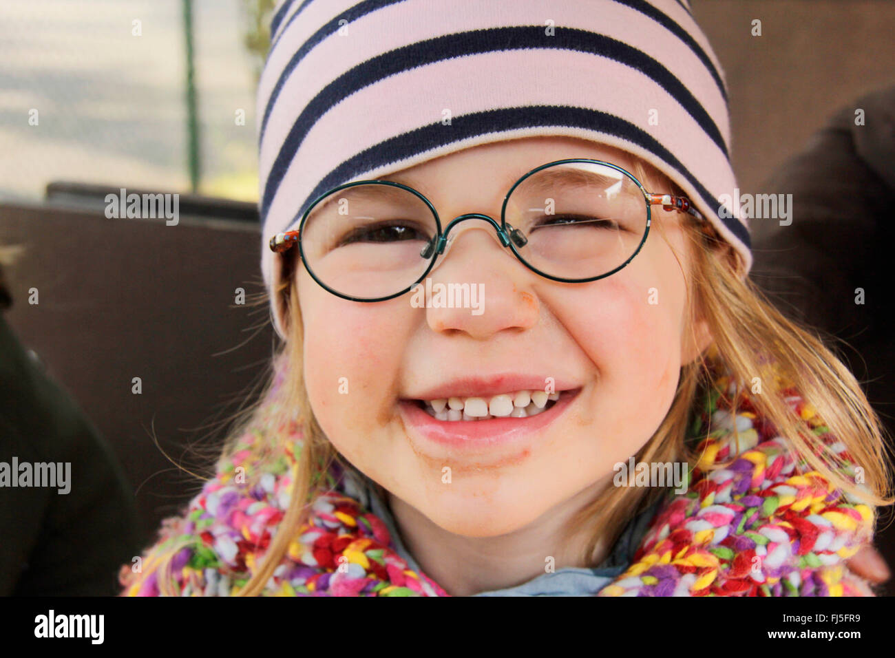 smiling little girl with glasses, portrait of a child - Stock Image