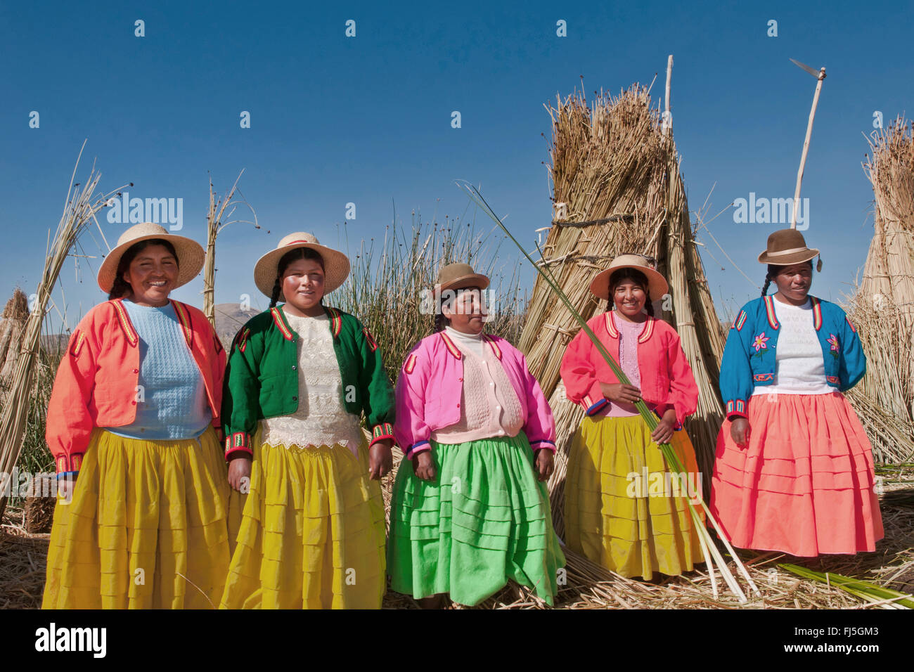 women of the Uros in traditional clothing on a swimming reed island, Uros at the totora harvesting, Peru, Andes - Stock Image