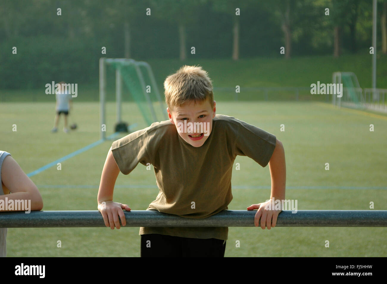 boy pressing himself above a railing on a football pitch, portrait of a child - Stock Image