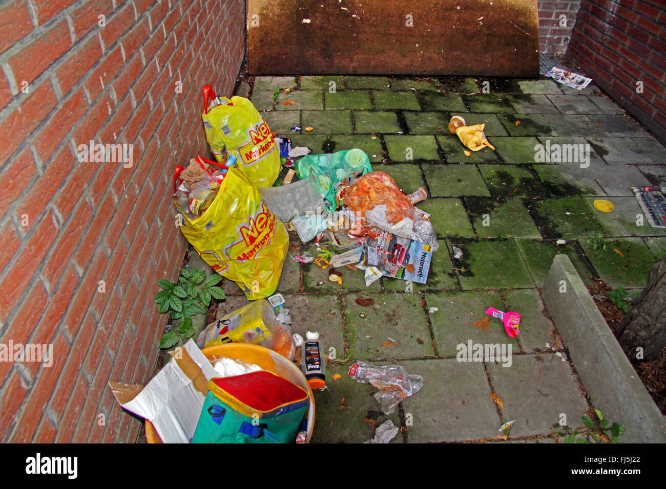 plastic bags full of waste between to houses, Germany - Stock Image