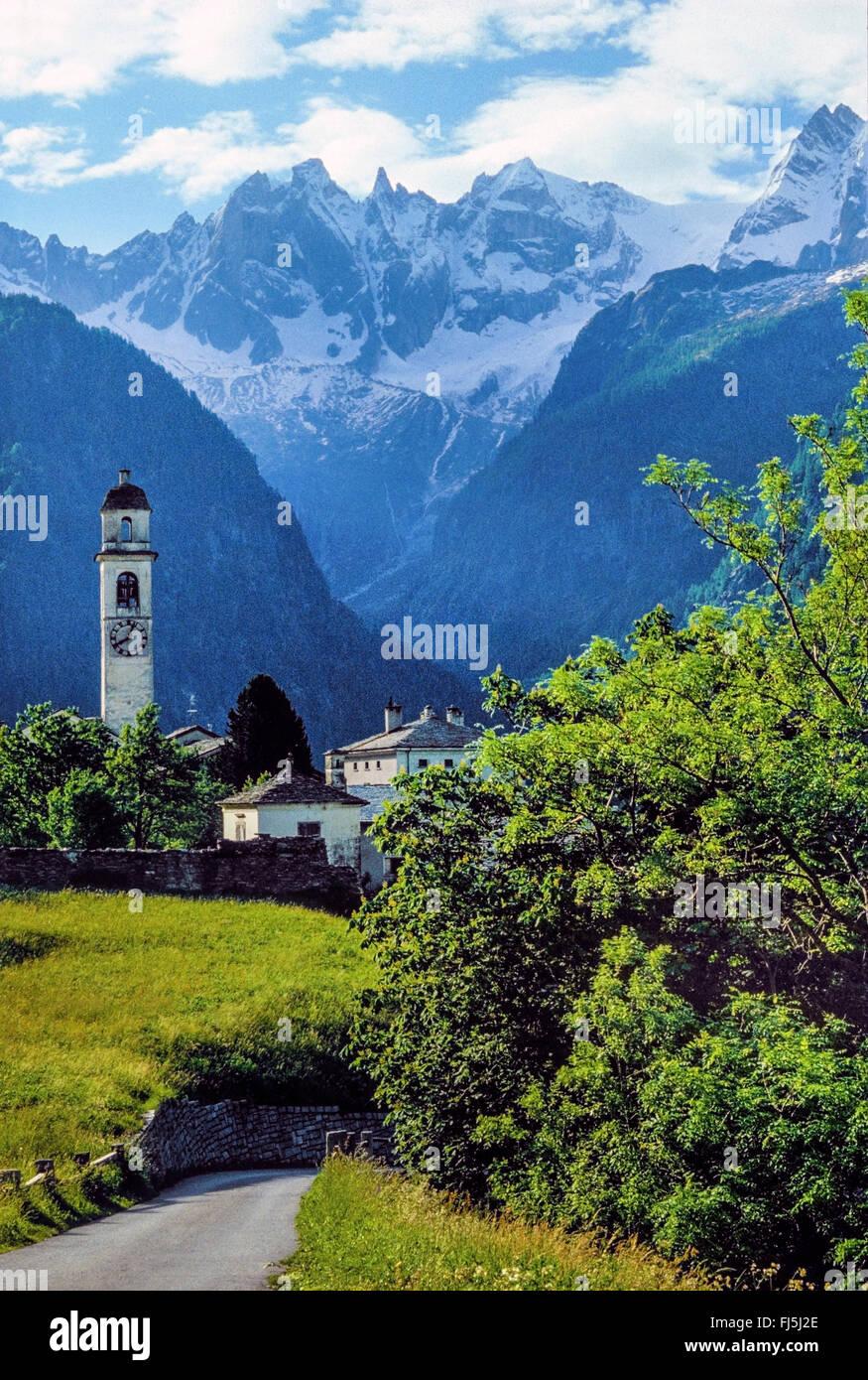 steeple of Soglio and Pizzo Badile and Cima della Bondasca, Switzerland, Grisons, Engadine, Bregaglia Stock Photo