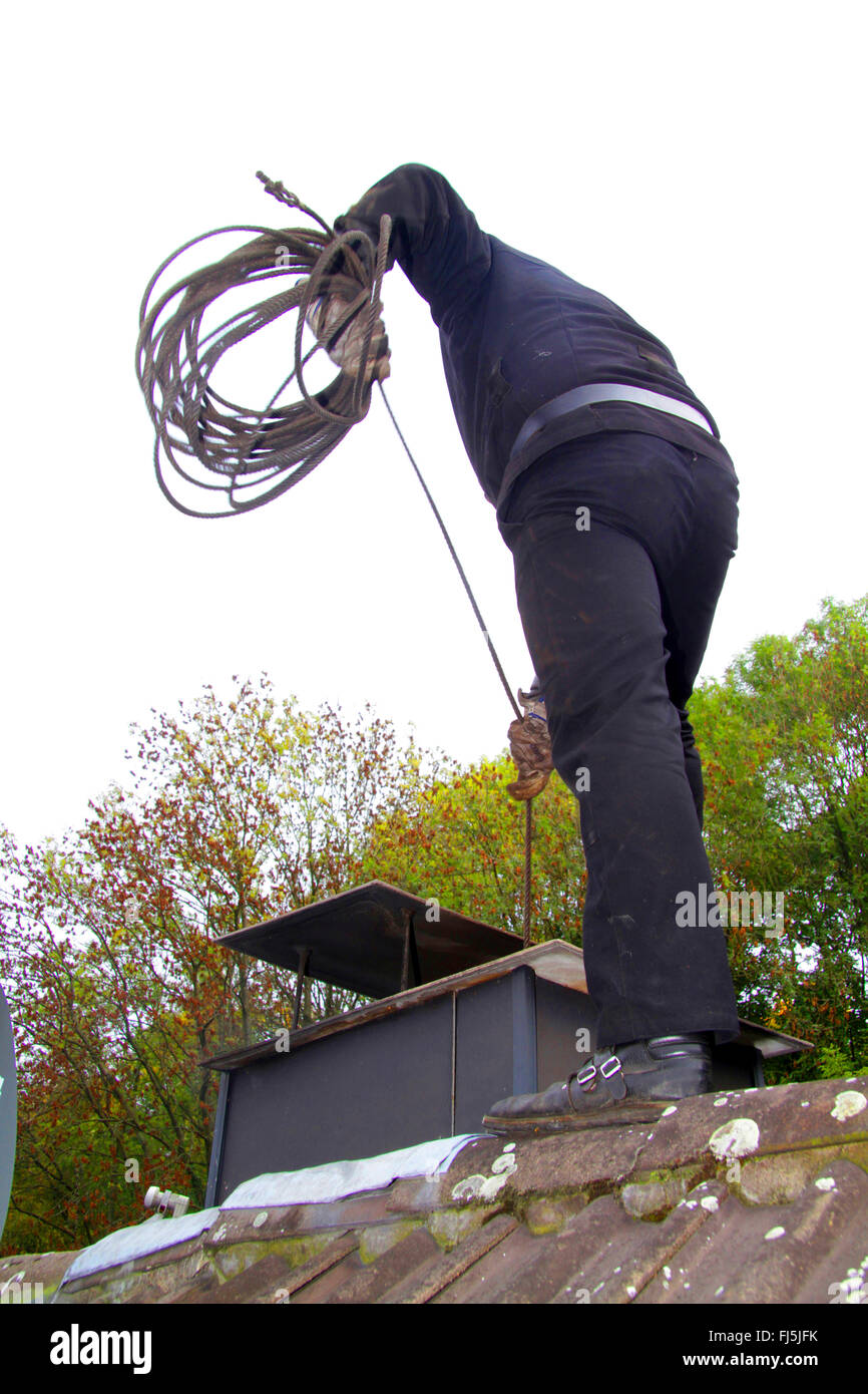 chimney sweeper at work on a roof, sweeping of a chimney, Germany - Stock Image