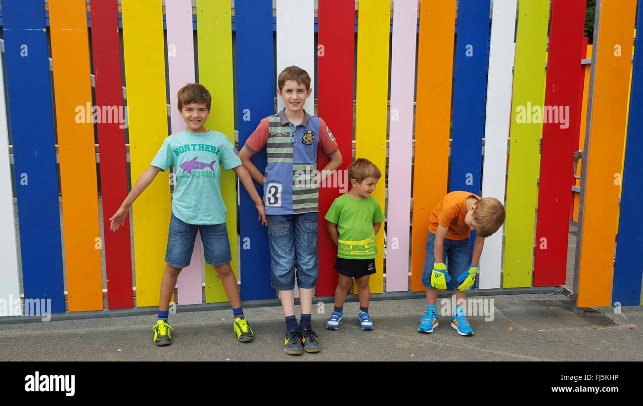four brothers standing in front of a colorful batten fence Stock Photo