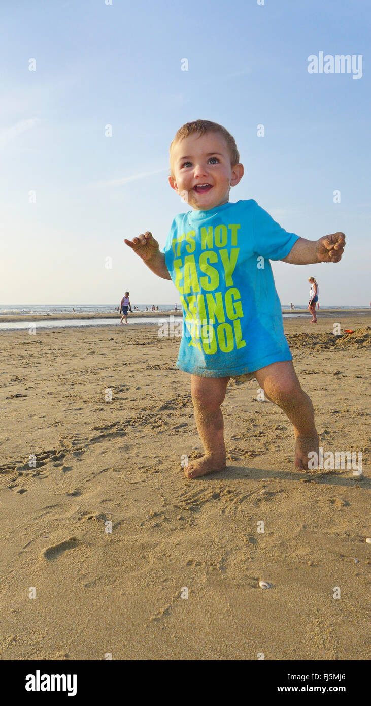 little laughing boy wearing a T-shirt on a sandy beach, Netherlands - Stock Image