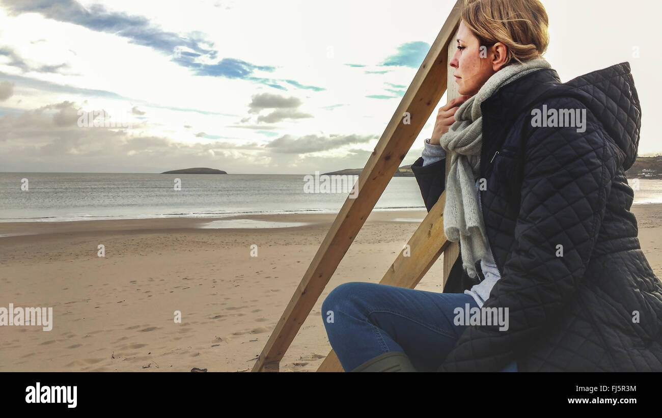 young woman sitting on wooden stairs on the beach - Stock Image