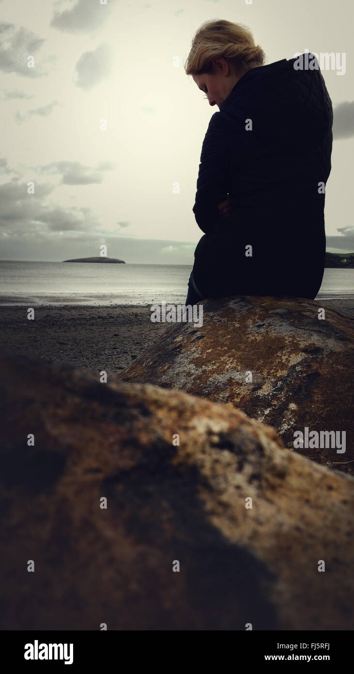 woman standing on beach by the rock - Stock Image