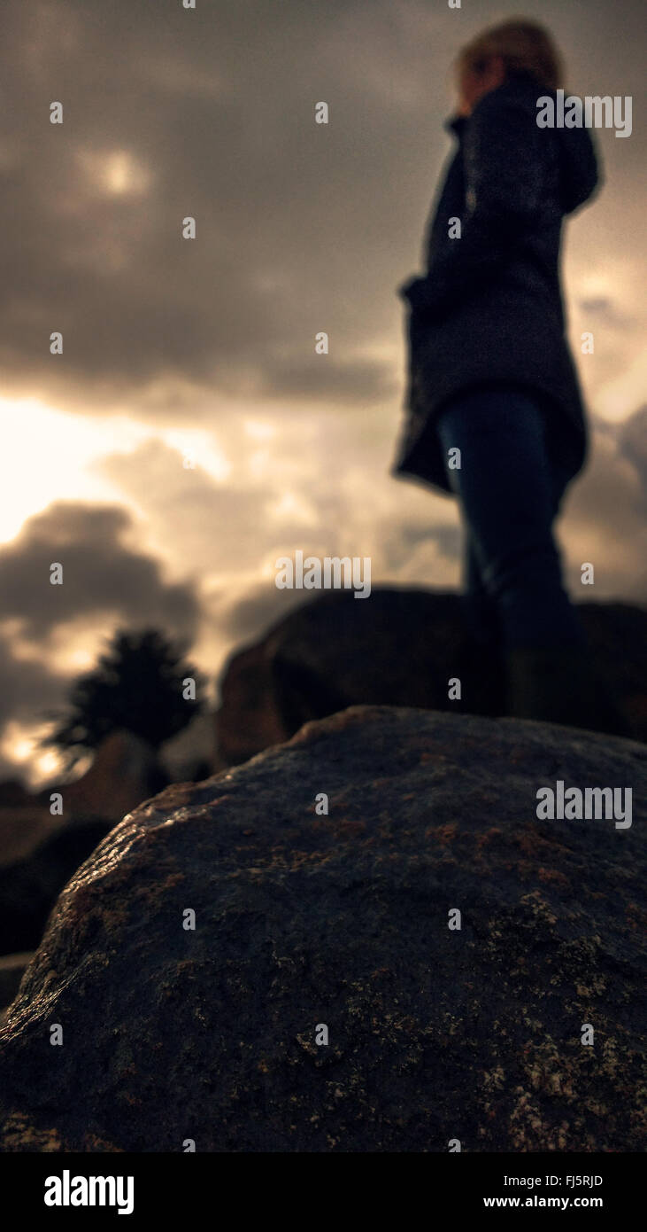 woman standing on rock in darkness - Stock Image