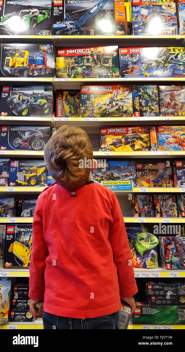 little boy admiring a plaything-shelf with LEGO packings Stock Photo