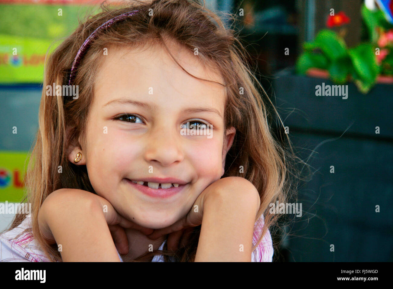 girl in good mood resting head on hands, portrait of a child, Germany - Stock Image