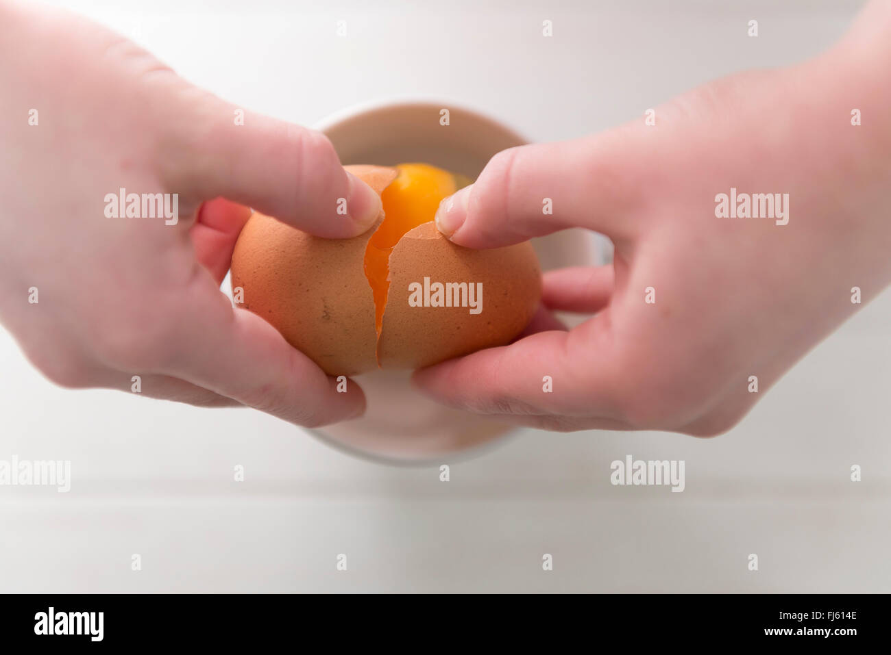 A cook cracking a free range egg in to a bowl. - Stock Image