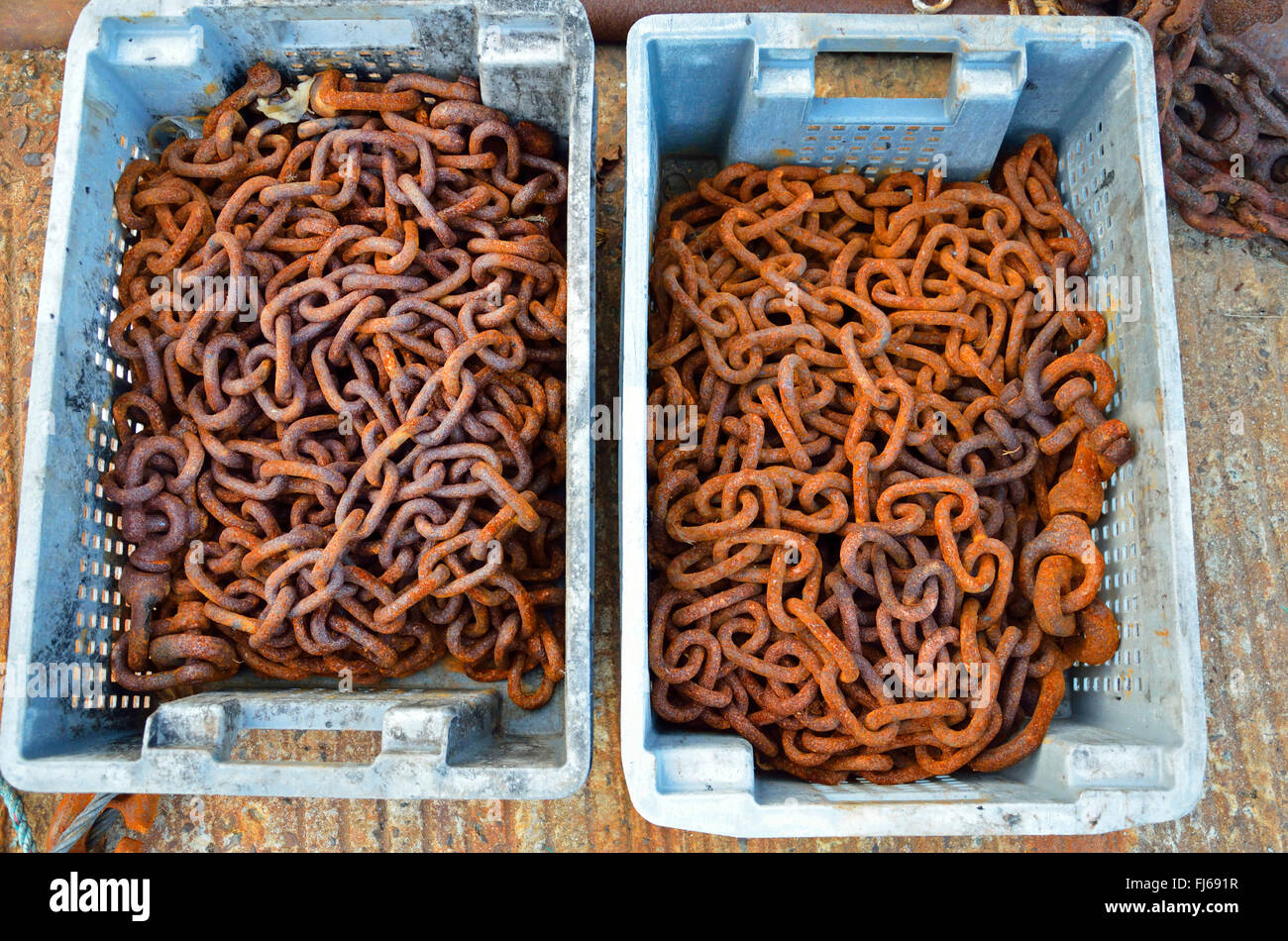 rusty chains in plastic boxes, France, Brittany - Stock Image