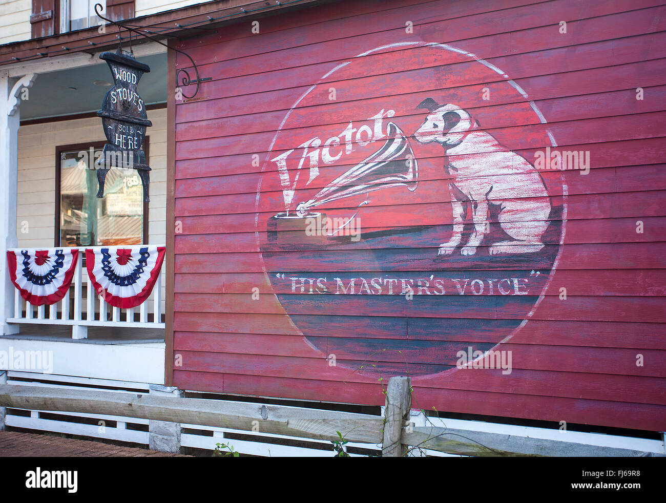 Images of a metal sign and the painted 'Victor' Logo and a fence with bunting on a shop that sells Wood - Stock Image