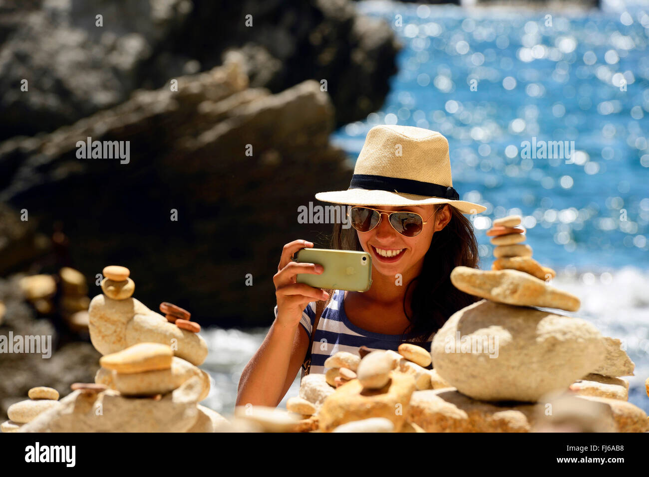 woman taking photos of piles of stones at the bottom of Stairway of the King of Aragon, France, Corsica, Bonifacio - Stock Image