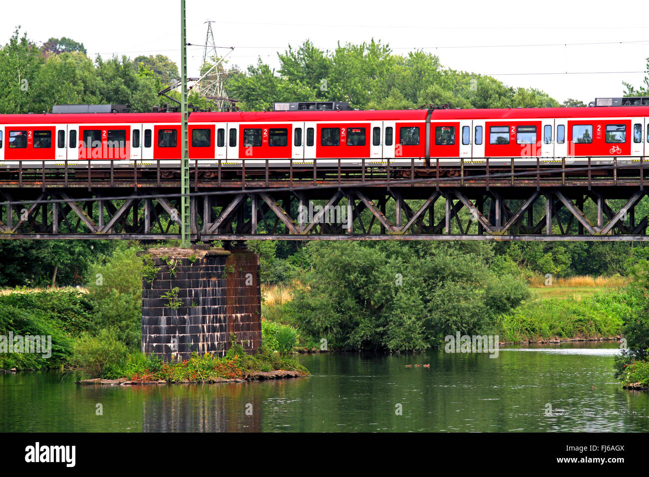 S-Bahn city train crossing the Ruhr river, Germany, North Rhine-Westphalia - Stock Image