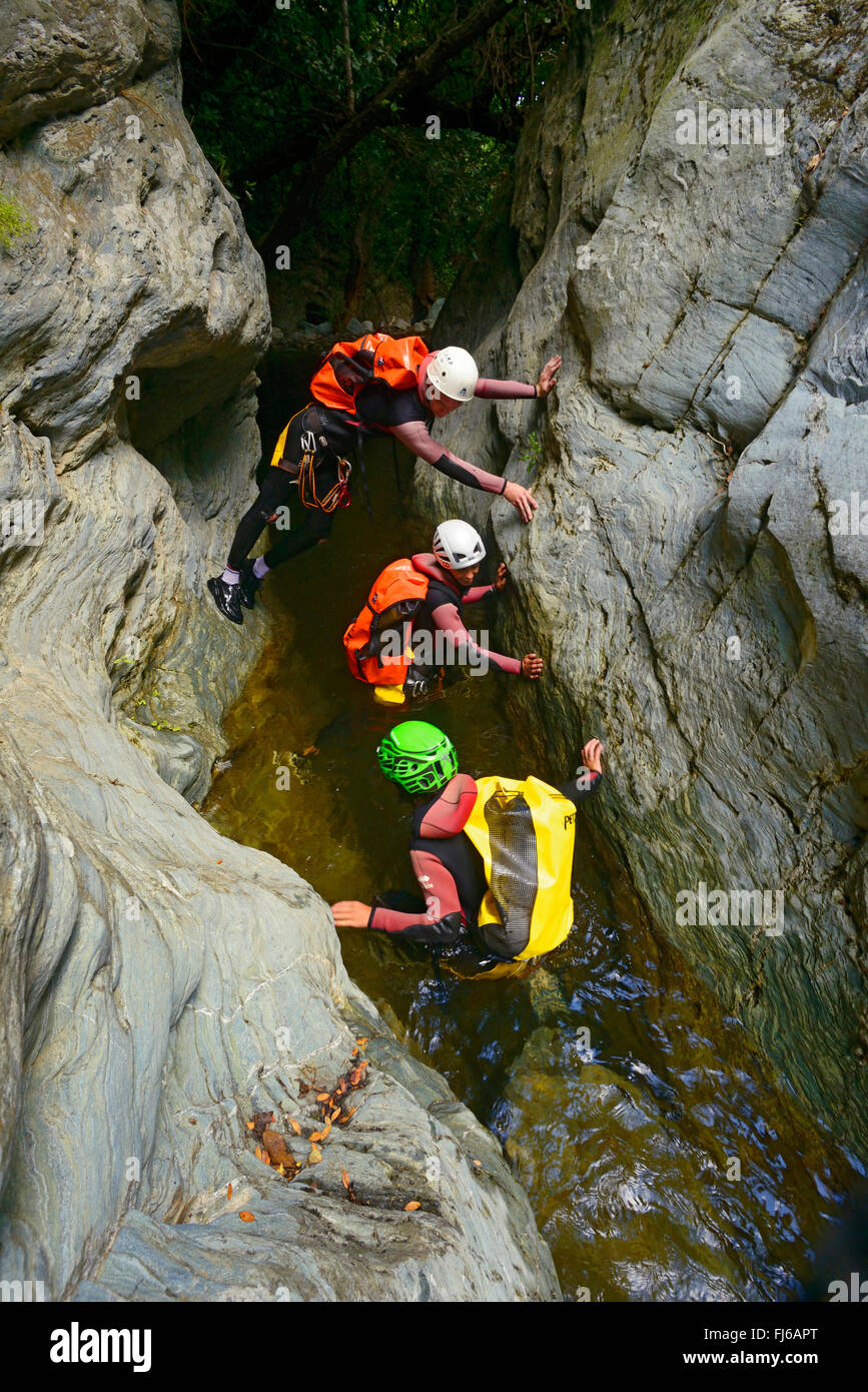three persons climbing through a canyon, France, Corsica, Bastia - Stock Image