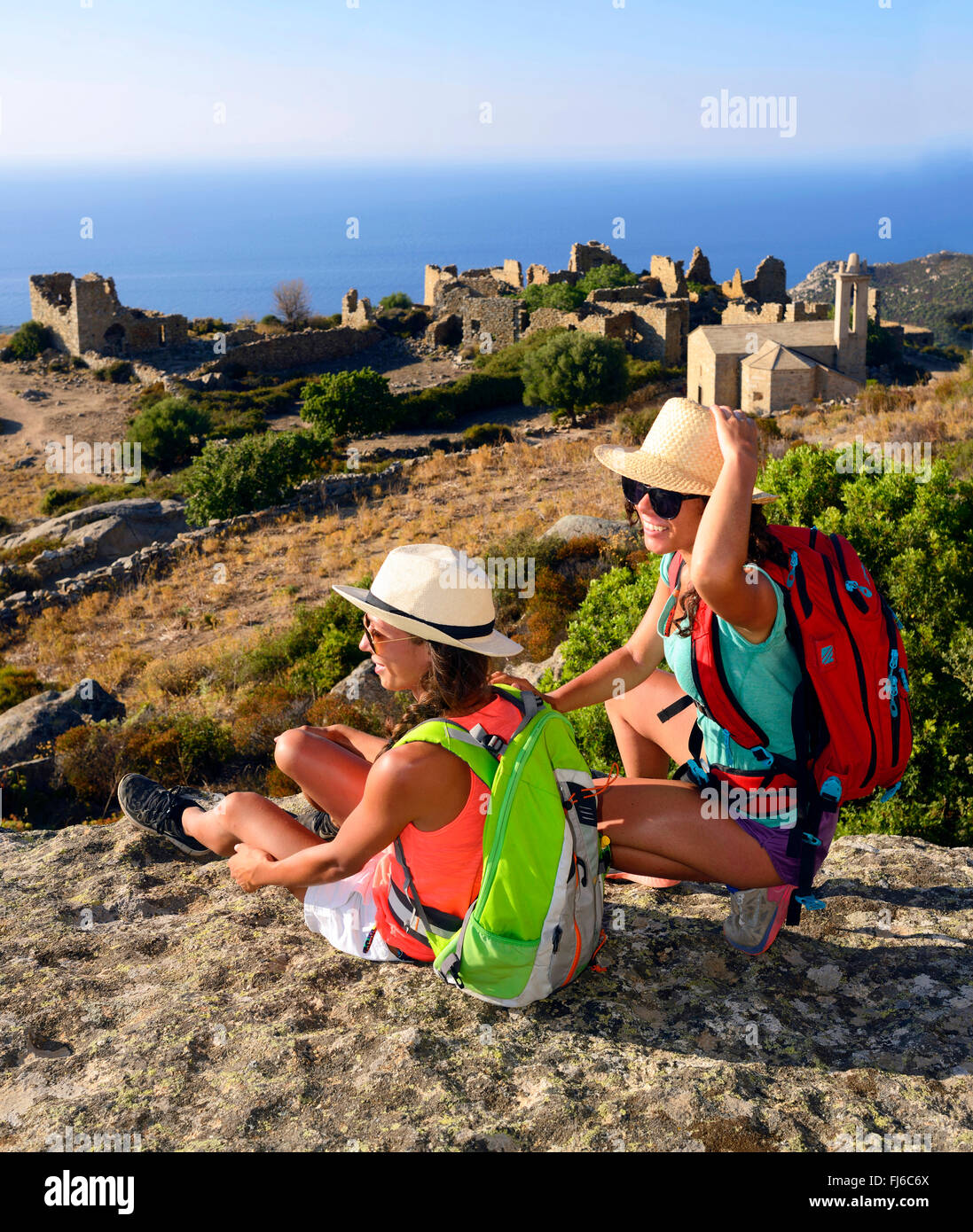 two female hikers taking a break, in the background the abandoned village ruins of Occi, France, Corsica - Stock Image