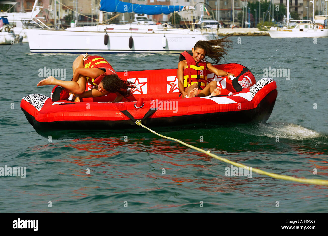 two girls are be pulled over the water with an air couch, France, Corsica - Stock Image