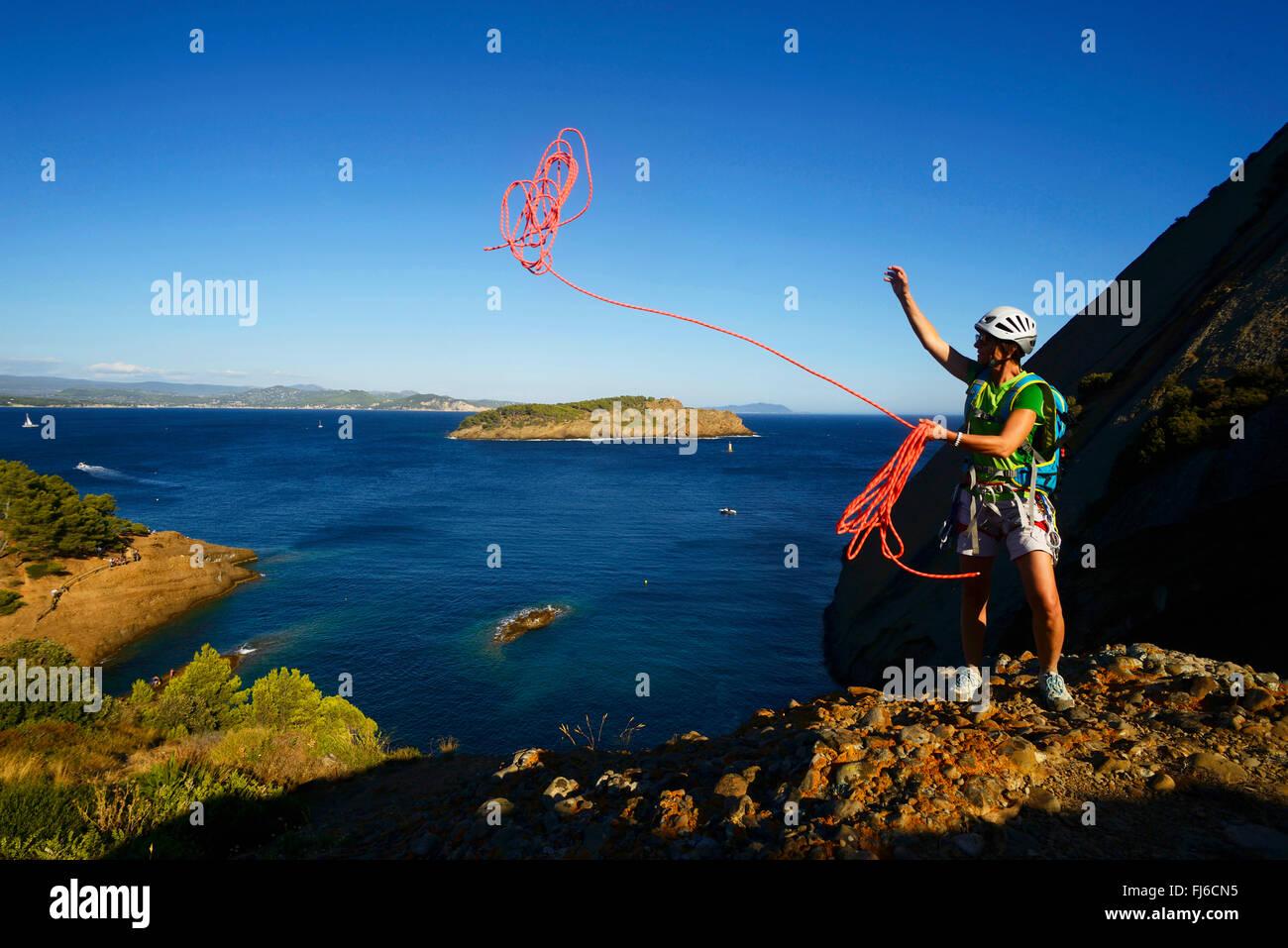 climber throwing a rope at coastal rock Bec de l'Aigle, adventure way, France, Provence, Calanques National - Stock Image