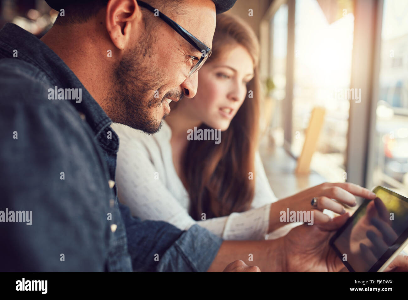 Happy young man with his girlfriend in a coffee shop surfing internet on digital tablet. Young couple in a restaurant - Stock Image