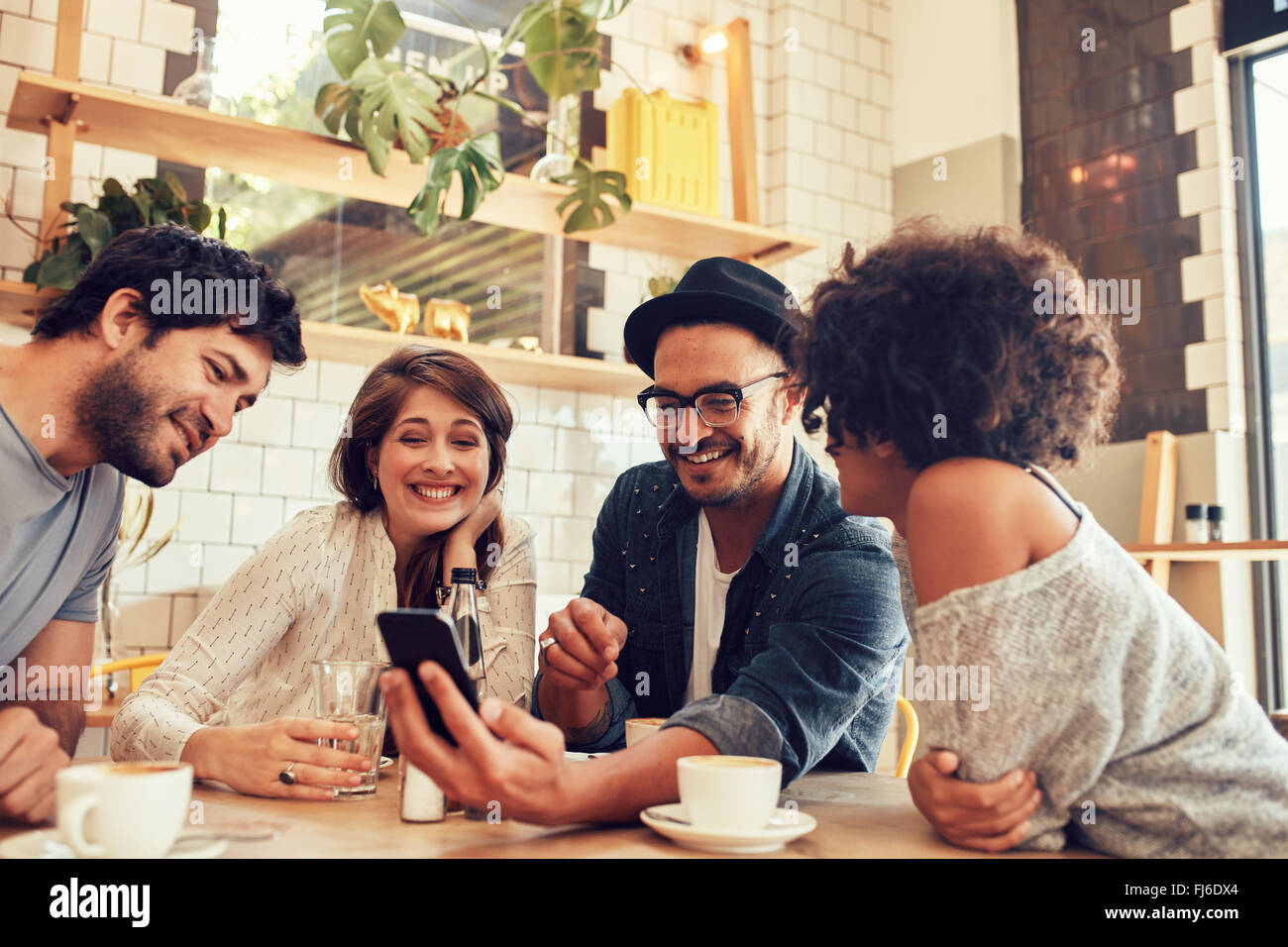 Portrait of a group of young friends meeting in a cafe and looking at the photos on mobile phone. Young men and - Stock Image