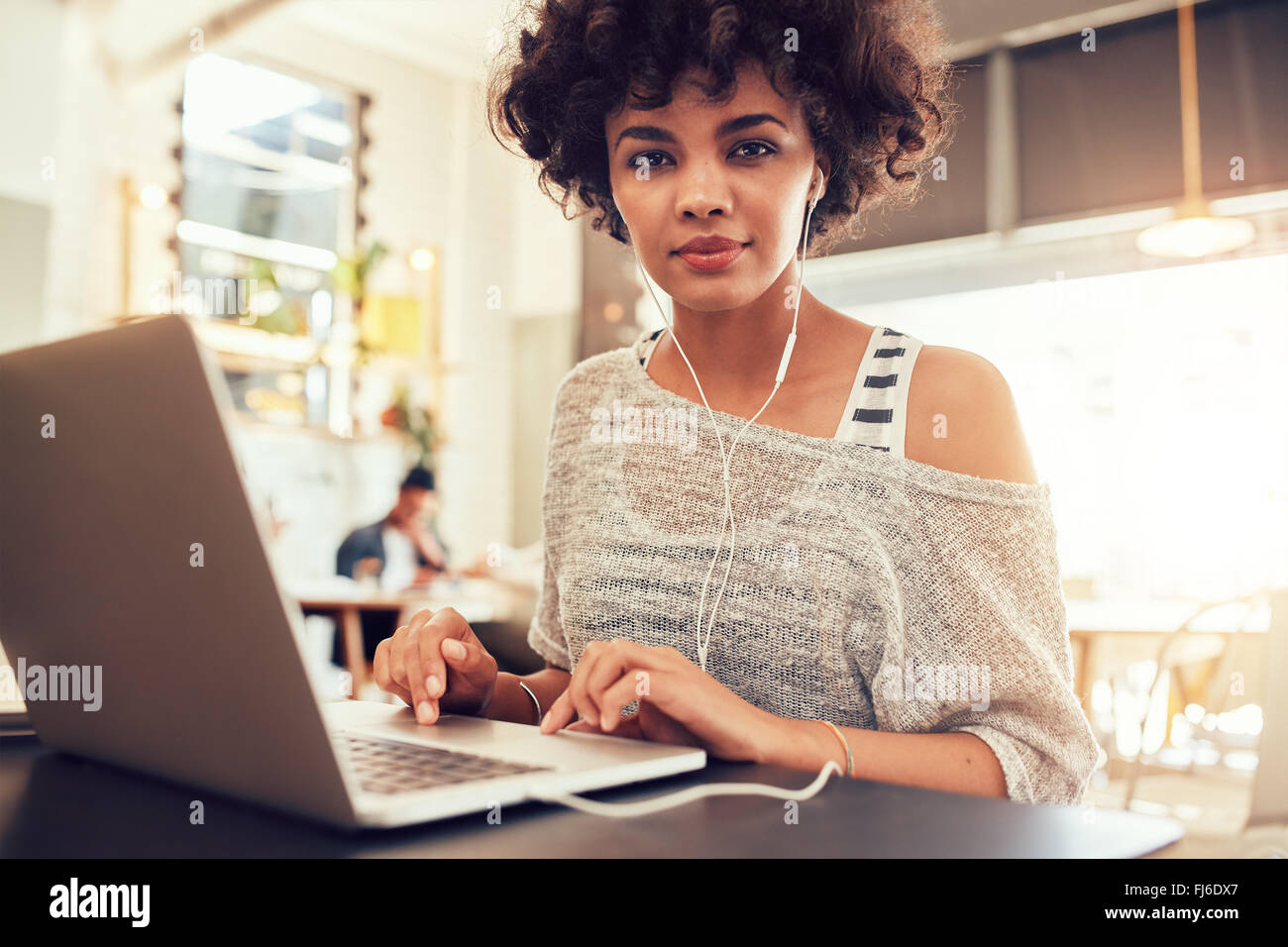 Portrait of young woman with a laptop at cafe. African woman sitting in coffee shop with a laptop. - Stock Image