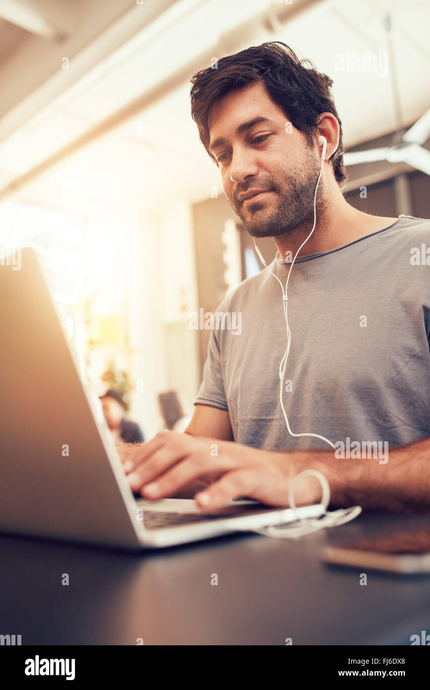 Portrait of young man looking busy working on laptop at a cafe. Caucasian man sitting in coffee shop using laptop. Stock Photo