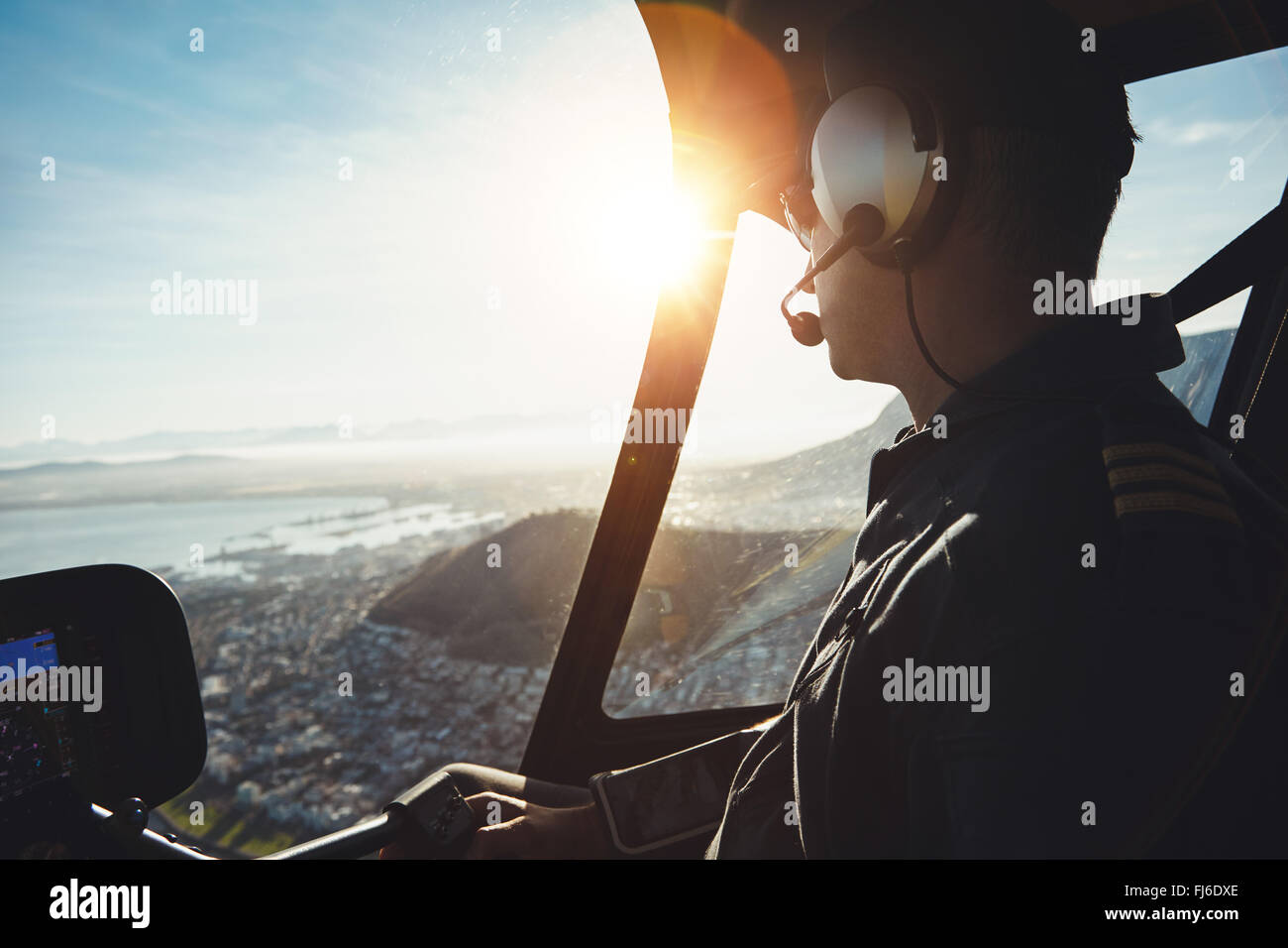 Close up of a helicopter pilot flying aircraft over a city on a sunny day - Stock Image